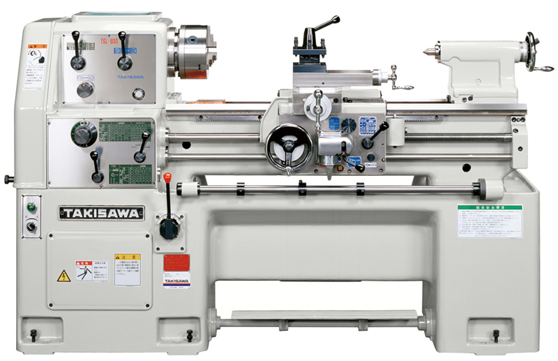 この画像は、株式会社滝澤鉄工所(Company)の旋盤切削加工機(TSL-Series 小型普通 精密旋盤)です。工作機械のなかでも旋盤は、横形でチャックという回転する台に加工物(ワーク)を固定し、バイトという工具でワークを切削して工作物を製作する機械です。画像の旋盤切削加工機(TSL-Series 小型普通 精密旋盤)は、国内外の多くの企業(Company)、製作所(works)、工場(factory)、教育訓練施設に納入、活用されています。工作実習(教育訓練)では、基礎/高度技能・技術の習得に適しています。また、標準で縦送り(長手方向)に自動停止装置や手前引き込み式起動レバー、フットブレーキが装備されており、一貫して安全性に配慮した設計となっていることも特徴です。このような普通旋盤やNC旋盤、マシニングセンタなどの工作機械は、摺動面を飛散する切粉や切削液から保護する(ガード)必要があります。自社では切屑から機械を保護するテレスコピックカバー(テレスコカバー)、テレスコボックスも得意としています。機械カバーに関するご相談、ご要望、お見積り依頼などありましたら、お問い合わせフォーム、tel、faxでお気軽にお問い合わせください。